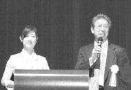 総合司会の丸岡 敬 保証・教育研修委員長と司会の水上アナ