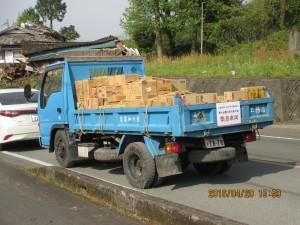 (公社)全日本不動産協会緊急車両の支援物資トラックとその奥の倒壊家屋